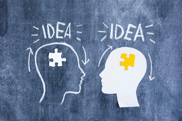 Ideentext über dem gehirn mit weißem und gelbem puzzlen auf tafel Kostenlose Fotos