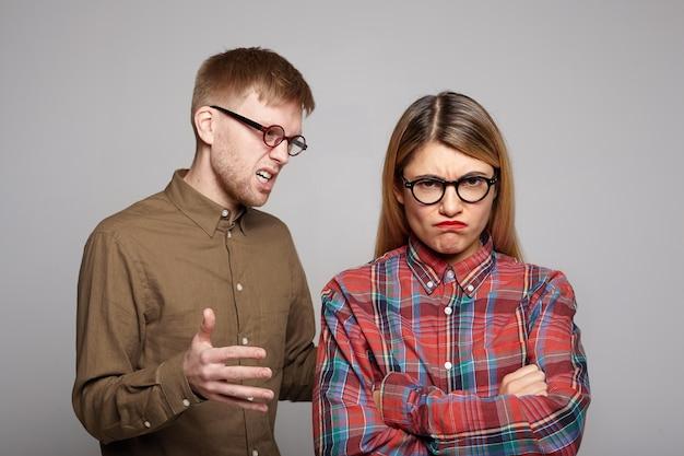 Ihr europäisches ehepaar hat streit: bärtiger mann in einer ovalen brille, der versucht, seine störrische freundin zu überzeugen, die die arme verschränkt und eine unzufriedene grimasse zieht und uneinigkeit ausdrückt Kostenlose Fotos