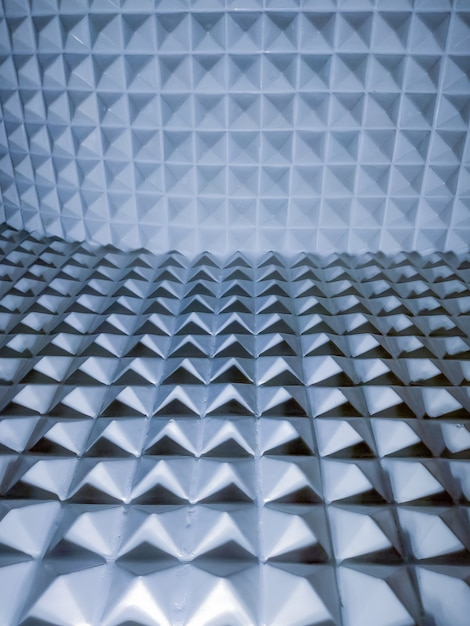 Illusion von scharfen pyramidenförmigen kunststoffelementen geometrisch strukturiert und hintergrund. Premium Fotos