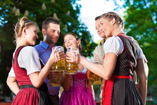 Im biergarten - freunde, die bier trinken Premium Fotos
