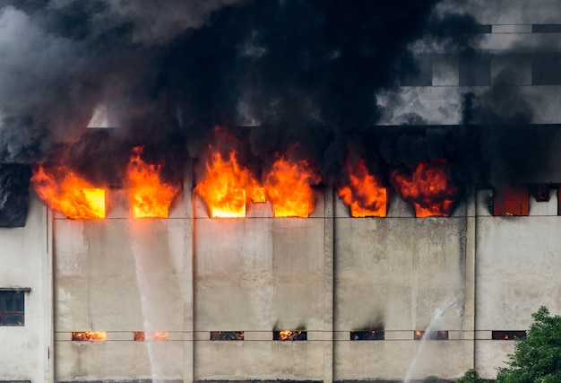 Im lagerhaus brach ein feuer aus und die feuerwehr löschte das feuer. Premium Fotos