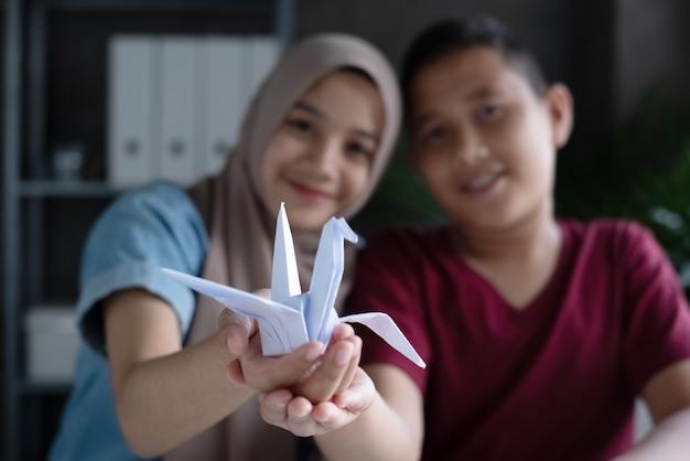Im selektiven fokus des papierfaltvogels in den moslemischen studentenhänden Premium Fotos