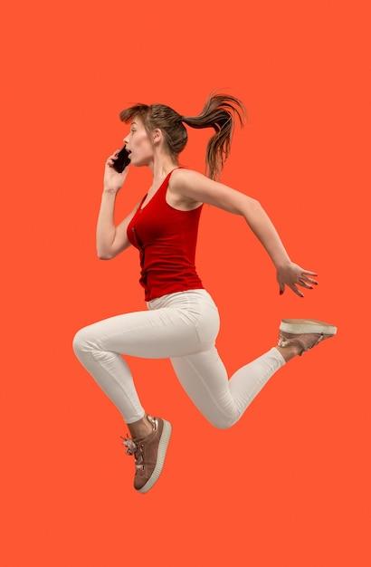 Immer mobil. volle länge der hübschen jungen frau, die telefon nimmt, während sie gegen rotes studio springt. Kostenlose Fotos