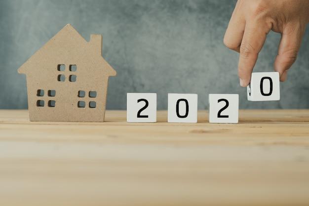 Immobilien im jahre 2020, abschluss herauf hand setzten zahl mit holz des kleinen hauses auf tabelle Premium Fotos