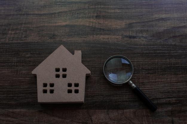 Immobilien- und inspektorkonzept, hausmodell und lupe auf hölzerner tabelle Premium Fotos