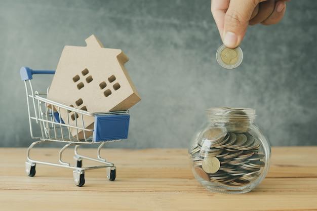 Immobilien und kaufendes und verkaufendes hauptkonzept, hand steckten geldmünze in glas und hausmodell in den wagen Premium Fotos