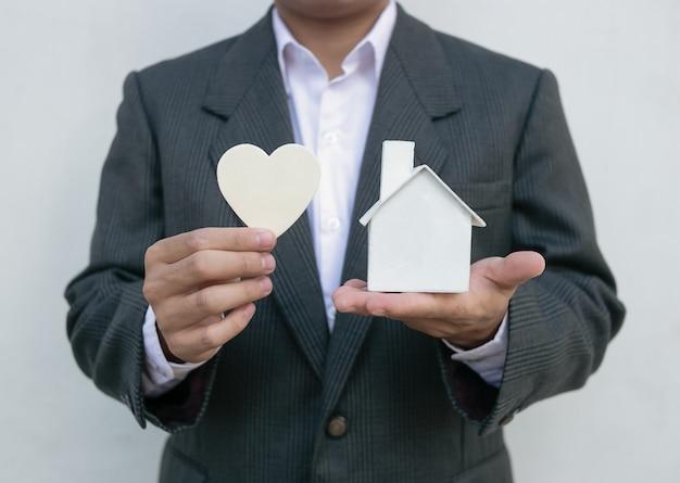 Immobilienagentur mit hausmodell und weißem herzen Premium Fotos
