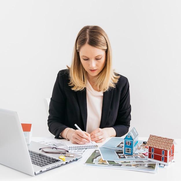 Immobiliengeschäftsfrau, die im büro arbeitet Kostenlose Fotos