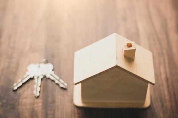 Immobilienhaus und wohngeschäftskonzept, hausmodell und schlüsselplatz auf hölzerne tabelle Premium Fotos