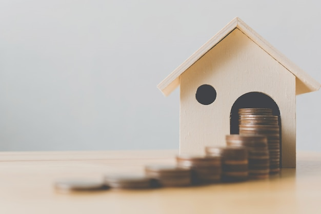 Immobilieninvestitions- und haushypothekenfinanzkonzept, geldmünzenstapel mit holzhaus Premium Fotos