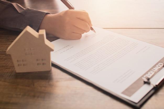 Immobilienkonzept, kunde oder hauskäufer unterzeichnen auf vertragspapier Premium Fotos