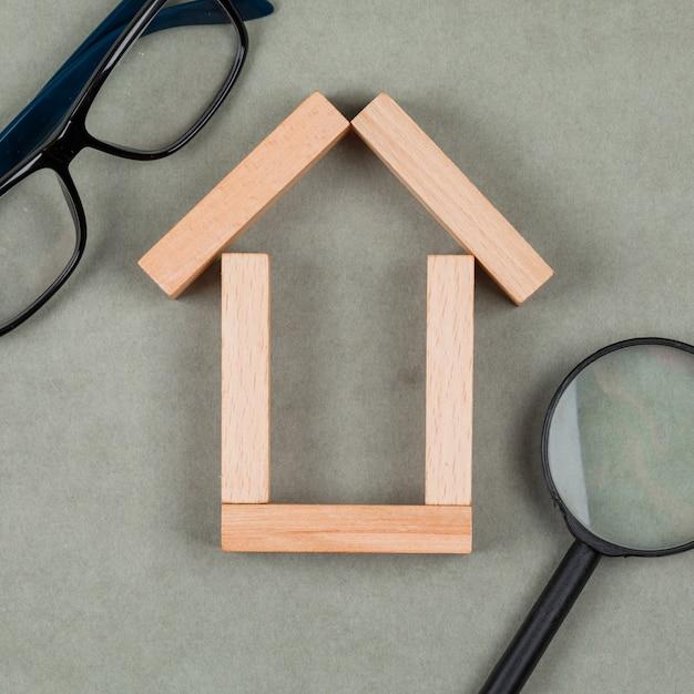 Immobilienkonzept mit haus aus holzklötzen, gläsern, lupe auf grauer hintergrundnahaufnahme. Kostenlose Fotos