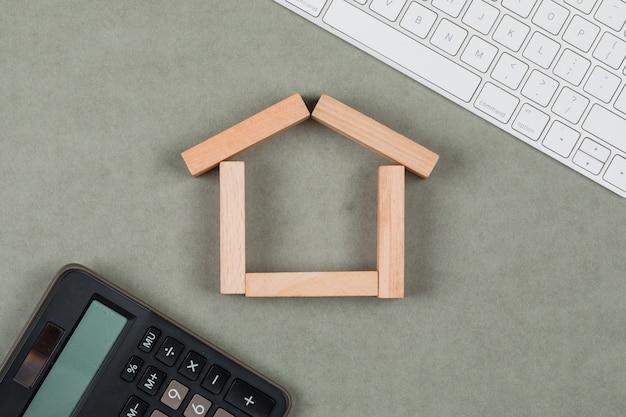 Immobilienkonzept mit holzklötzen, taschenrechner, tastatur auf grauem hintergrund flach legen. Kostenlose Fotos