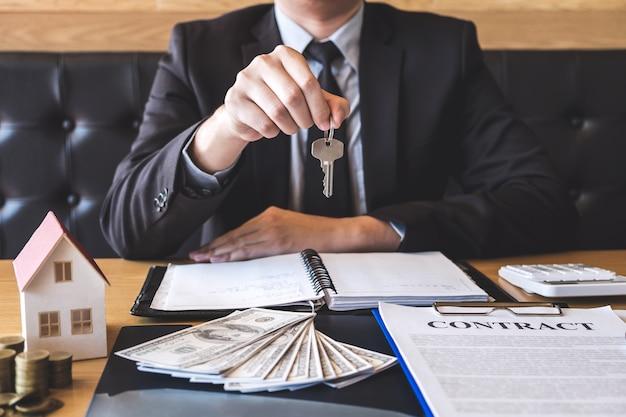 Immobilienmakler, der dem kunden hausschlüssel gibt, nachdem vertragszustand mit genehmigt unterzeichnet worden ist Premium Fotos