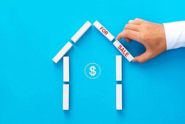 Immobilienmakler, der ein haus aus holzklötzen mit text zum verkauf baut. Premium Fotos