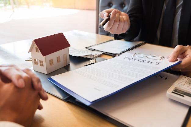 Immobilienmakler, der hausschlüssel-kundenvereinbarungseigenschaft zum verkauf gibt Premium Fotos