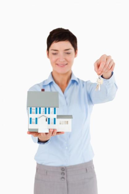 Immobilienmakler, der schlüssel und ein miniaturhaus zeigt Premium Fotos
