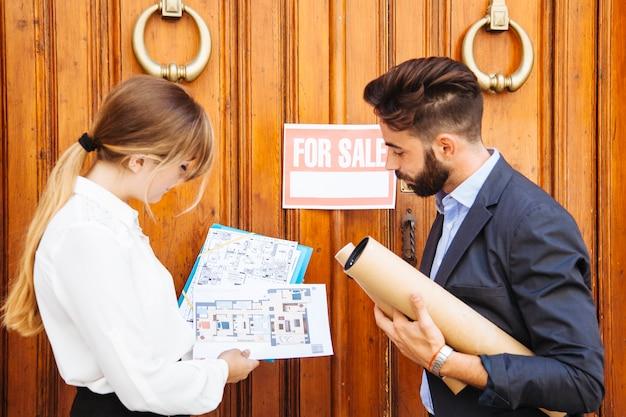 Immobilienmakler warten mit plänen vor der tür Kostenlose Fotos