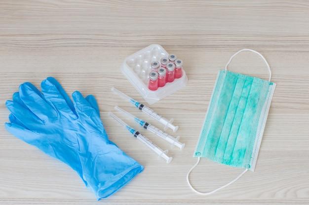 Impfampullen, spritzen, handschuhe und eine schutzmaske Premium Fotos