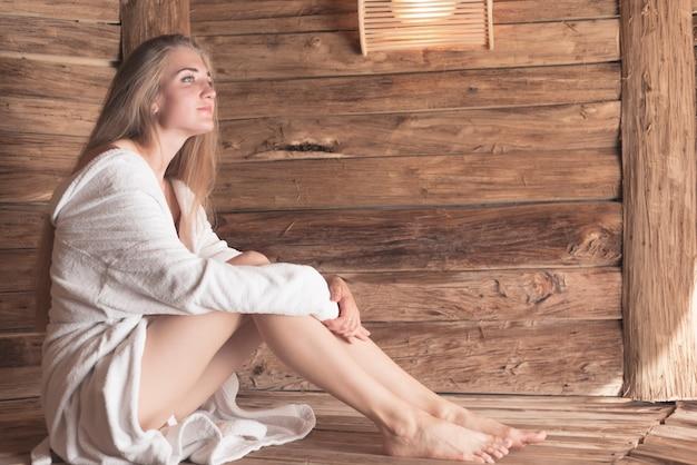 In betracht gezogene schöne junge frau, die in der sauna