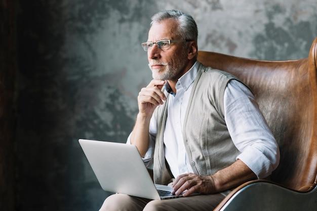 In betracht gezogener älterer mann, der auf stuhl mit laptop gegen schmutzhintergrund sitzt Kostenlose Fotos