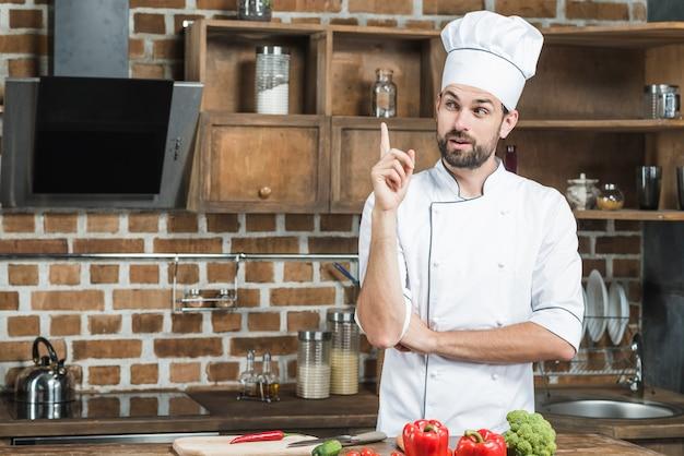 In betracht gezogener männlicher chef in der küche den finger aufwärts zeigend Kostenlose Fotos