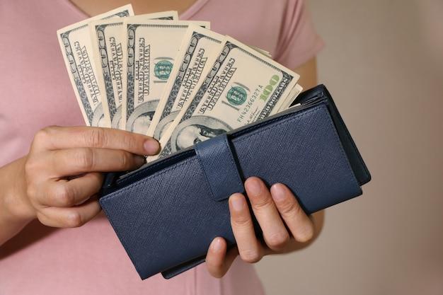 In den händen der frauen befindet sich die brieftasche aus leder mit einem bündel von hundert dollar. Premium Fotos