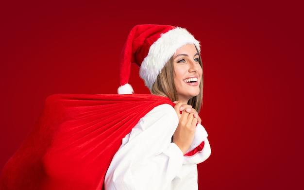 In den weihnachtsferien junge blonde frau, die eine tasche voll der geschenke aufhebt Premium Fotos
