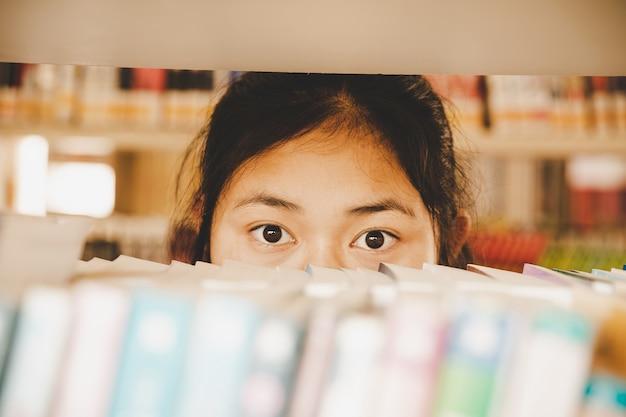In der bibliothek - junge studentin mit büchern, die in einer high school-bibliothek arbeiten. Kostenlose Fotos
