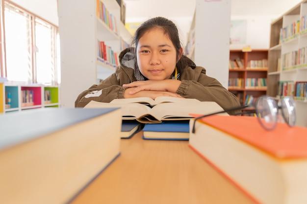 In der bibliothek - junge studentin mit büchern, die in einer highschool-bibliothek arbeiten. Kostenlose Fotos