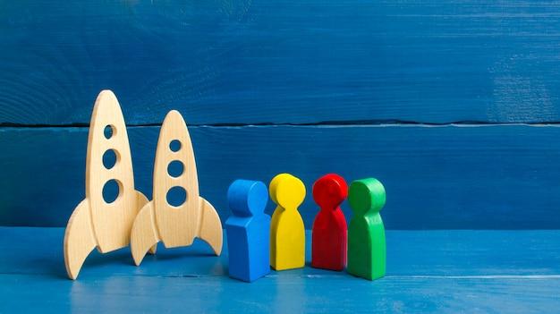 In der nähe von raketen stehen bunte figuren von menschen. Premium Fotos
