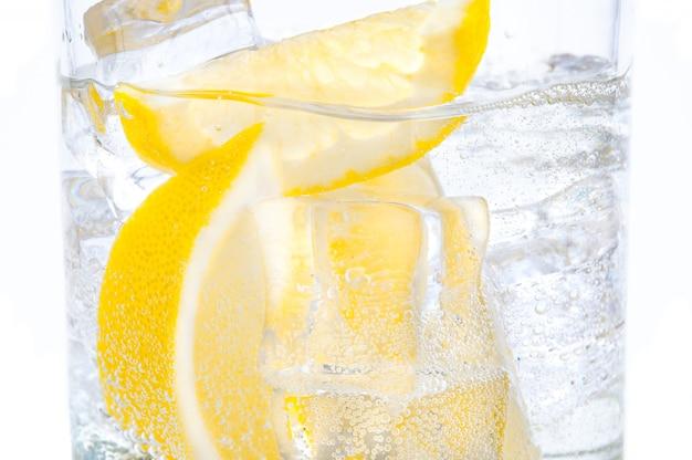 In einem glas mit würfeln schmelzender eisscheiben einer saftigen zitrone. Premium Fotos