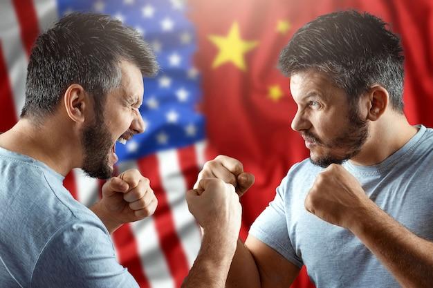 In einem handelskrieg zwischen china und den vereinigten staaten bereiten sich zwei männer auf einen kampf vor dem hintergrund der amerikanischen und chinesischen flagge vor. waffenstillstand, krieg, sanktionen, geschäfte. Premium Fotos