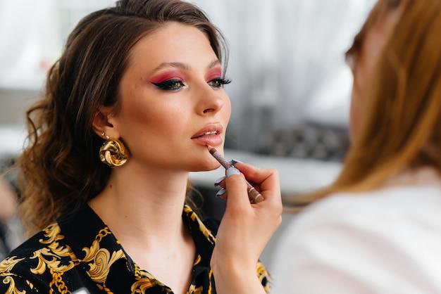 In einem schönen, modernen schönheitssalon macht ein professioneller make-up-stylist make-up für ein junges mädchen. schönheit und mode. Premium Fotos