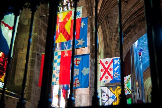 In einer schottischen kirche in edinburgh hingen flaggen mehrerer schottischer und englischer clans. Premium Fotos