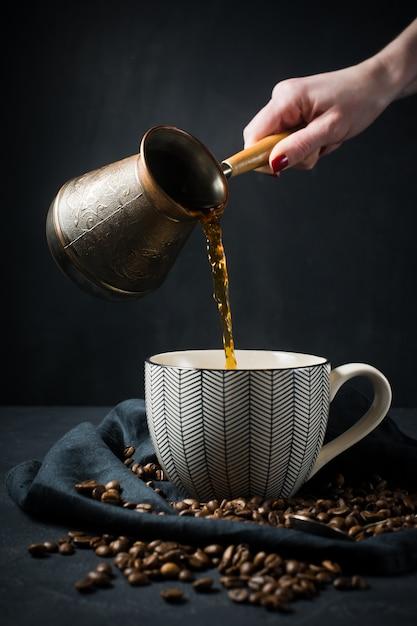 In einer tasse gießt eine frauenhand türkischen kaffee von den türken. Premium Fotos