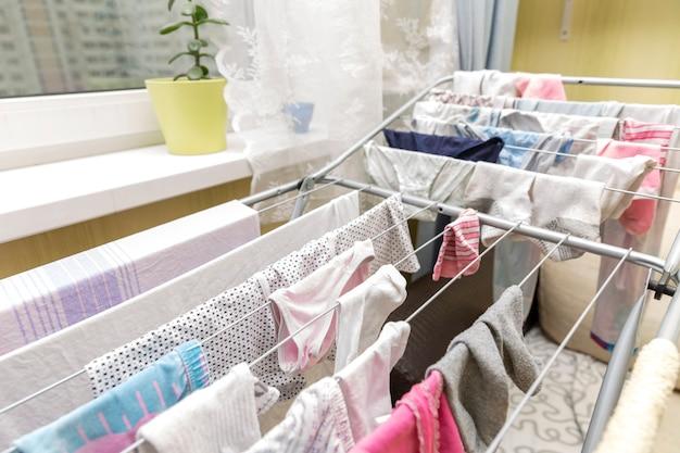 In einer wohnung in der nähe des fensters hängt wäsche an einem trockner. Premium Fotos