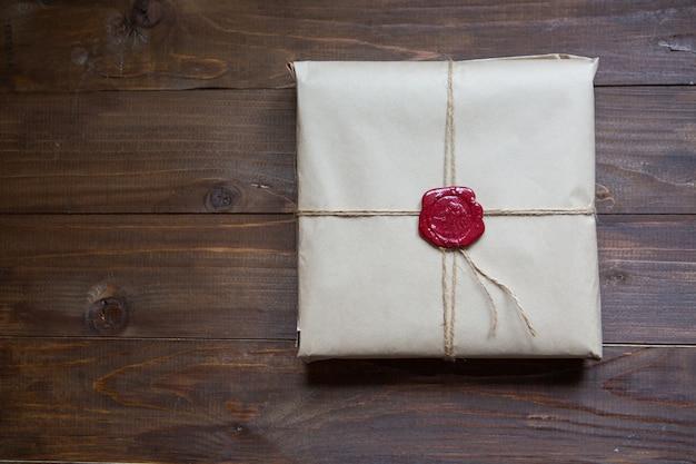 In kraftpapier eingewickeltes geschenk, mit schnur und geklebtem wachssiegel. auf dem tisch liegen mit platz für text Premium Fotos