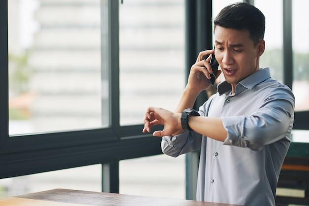 In panik versetzender asiatischer mann, der am handy spricht und armbanduhr betrachtet Kostenlose Fotos