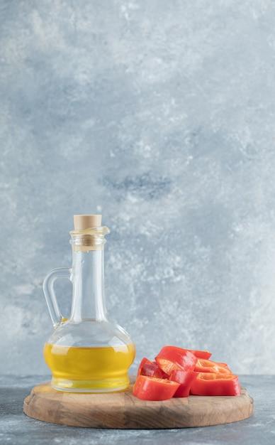 In scheiben geschnitten von süßem rotem paprika mit einer glasflasche öl auf holzbrett. Kostenlose Fotos