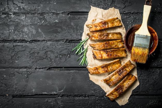 In scheiben geschnittene gegrillte rippen mit sauce. auf einem schwarzen rustikalen hintergrund. Premium Fotos