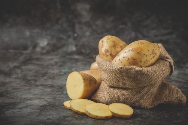 In scheiben geschnittene kartoffeln um den kartoffelsack auf grauem boden legen Kostenlose Fotos