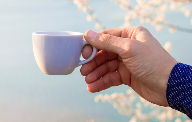 In seiner hand eine tasse auf blauem grund Premium Fotos