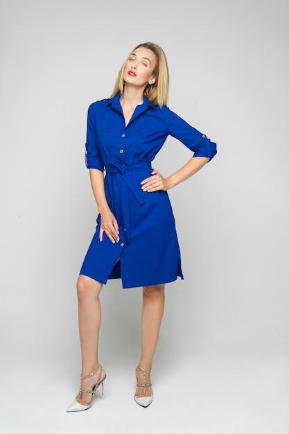 In voller länge stock photo porträt einer trendigen erwachsenen frau mit blonden haaren tragen formale hellblaue kleid mit knöpfen Premium Fotos
