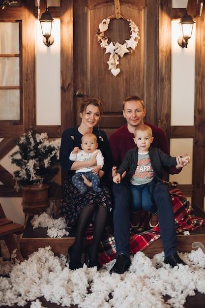 In voller länge stock photo von liebenden ehemann und ehefrau mit zwei kindern auf ihren beinen küssen Premium Fotos