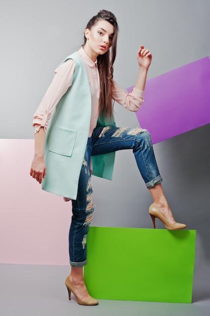 In voller länge vom schönen mädchen, mit grüner leerer werbetafel, über grauem hintergrund und rosa und violetter fahne Premium Fotos
