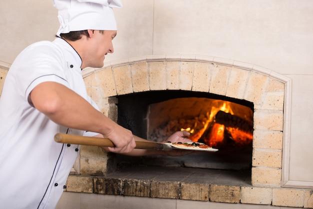 In weißer uniform kochen fügt ein gericht in den ofen. Premium Fotos