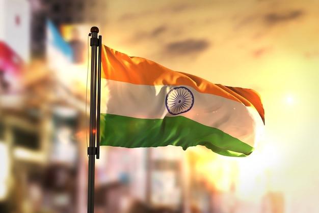 Indien flagge gegen stadt verschwommen hintergrund bei sonnenaufgang hintergrundbeleuchtung Premium Fotos