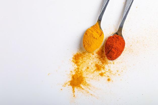 Indische gewürze paprikas und gelbwurzpulver im löffel auf weißem hintergrund Premium Fotos