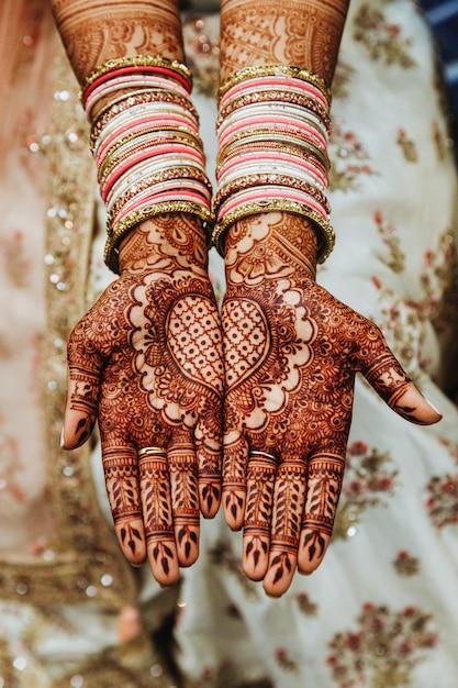 Indische hochzeitsarmbänder und mehandi hennastrauch färbten hände mit reflektierender verzierung Kostenlose Fotos